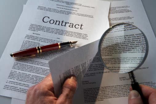Man's hands examining small print of contract with magnifying glass